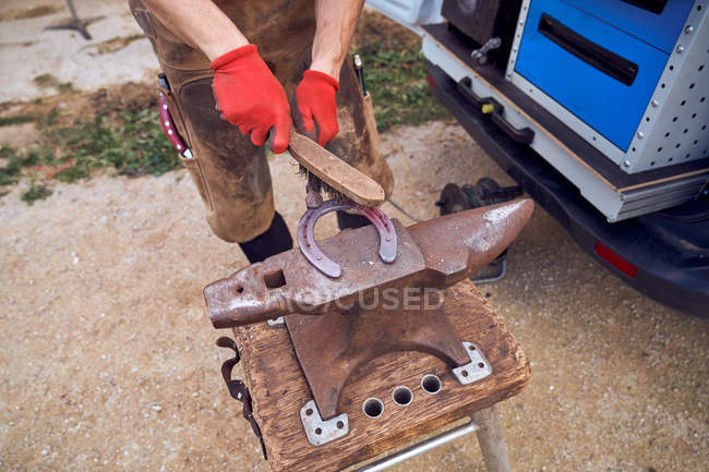 Вбитий нерозпізнаний коваль працює над ковадлом, змінюючи підкови на ногу з інструментами — стокове фото
