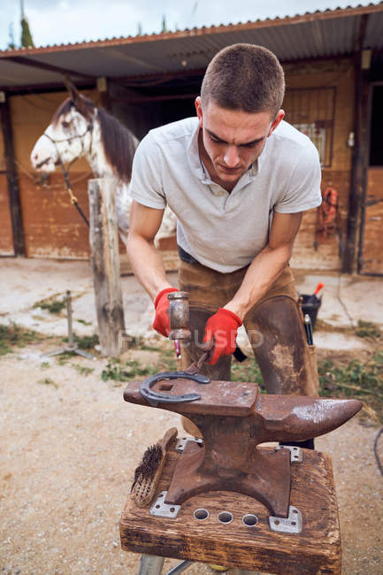 Blacksmith boy working on the anvil changing the horseshoe to a leg with tools — Stock Photo