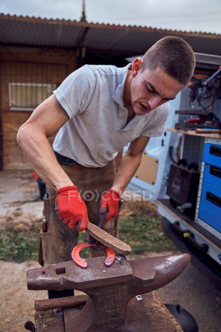 Хлопець з Блексміта працює над ковадлом, змінюючи підкови на ногу з інструментами. — стокове фото