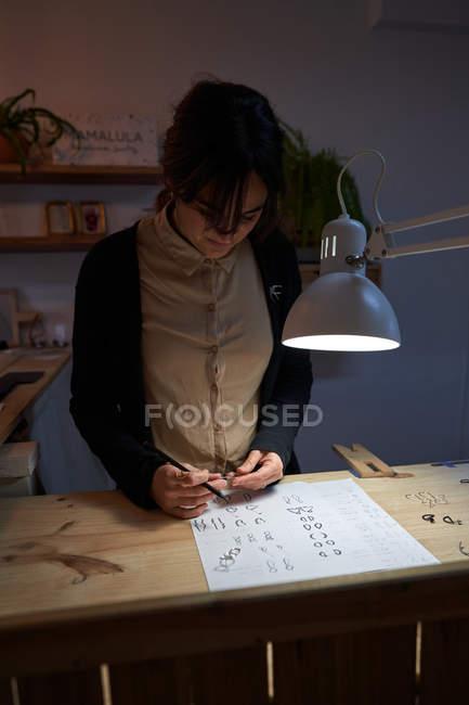 Красивая брюнетка ювелирные дизайнеры с карандашом в руке, делая ювелирные рисунки на бумаге на деревянном столе — стоковое фото