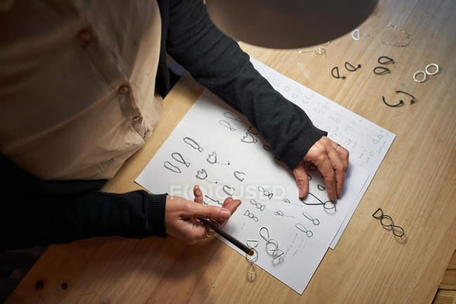 Невпізнавана жінка - ювелірні дизайнери з олівцем у руці роблять ювелірні малюнки на папері на дерев