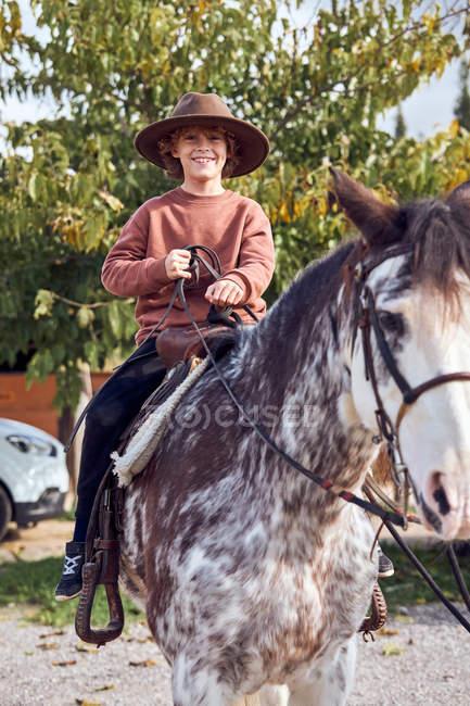Счастливый маленький мальчик в шляпе смотрит в камеру во время езды на своей коричневой лошади — стоковое фото
