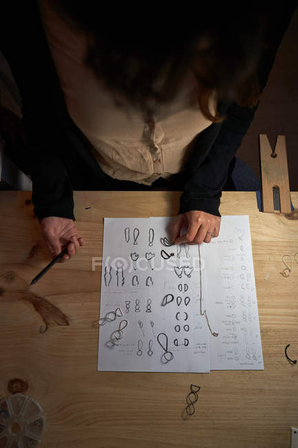 Cropped unrecognizable woman jewelry designers with a pencil in hand making jewelry drawings on a paper on a wooden table — Stock Photo