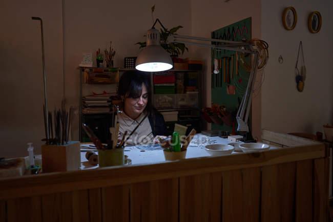 Красивая ремесленница-ювелирка работает в ювелирном магазине с инструментами и лампочкой — стоковое фото