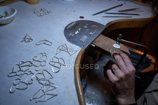 Обрезанный неузнаваемый ювелир женщина работает в ювелирном магазине, руки подробно с ювелирными изделиями и инструментами — стоковое фото