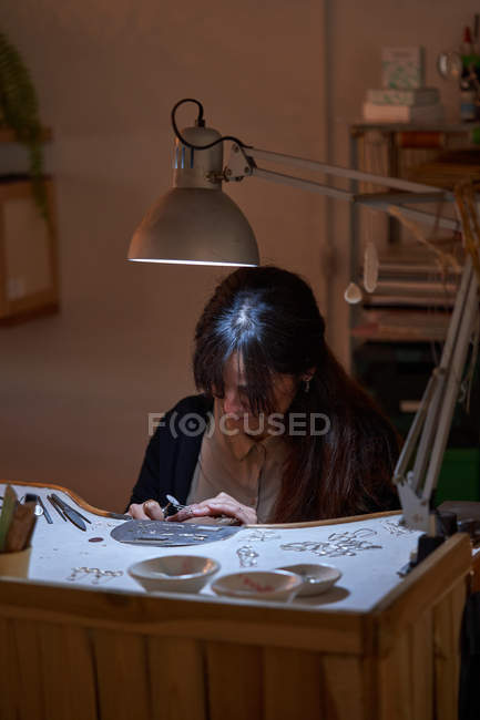 Beautiful artisan jeweler woman working in a jewelry shop with tools and a light bulb — Stock Photo