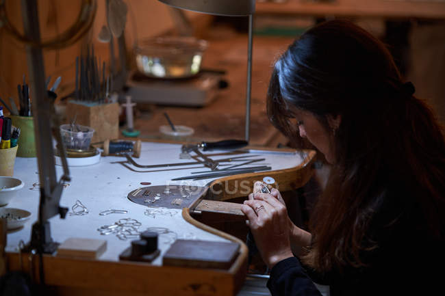 Beautiful artisan jeweler woman with working in a jewelry shop, hands detail with jewelry and tools — Stock Photo