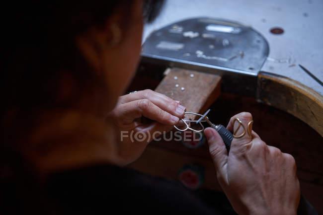 Geschnittene, unkenntlich gemachte Juwelierin, die in einem Juweliergeschäft arbeitet, überreicht Detail mit Schmuck und Werkzeug — Stockfoto