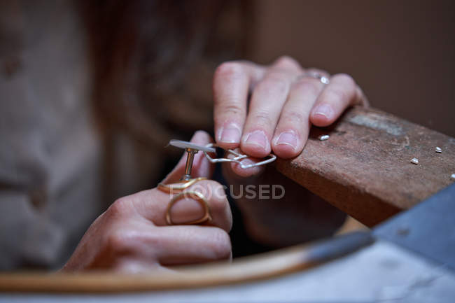 Cropped unrecognizable jeweler woman working in a jewelry shop, hands detail with jewelry and tools — Stock Photo