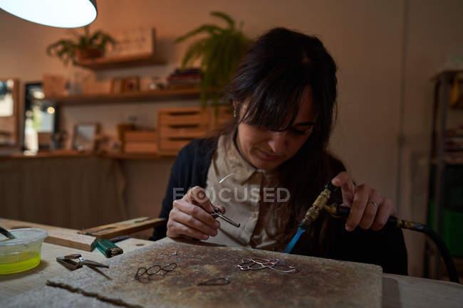 Artesã mulher joalheiro trabalhando com tocha jóias de solda — Fotografia de Stock