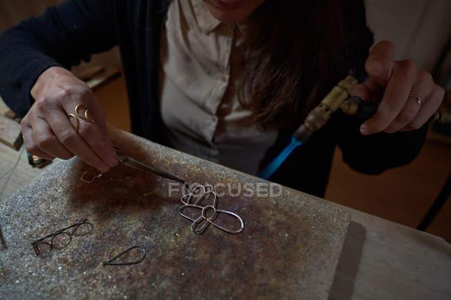 Обрезанная неузнаваемая ремесленница-ювелир, работающая с факелами для сварки драгоценностей — стоковое фото
