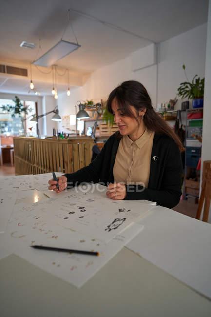 Женщина сидит за столом с карандашом, рисующим драгоценности на бумаге — стоковое фото