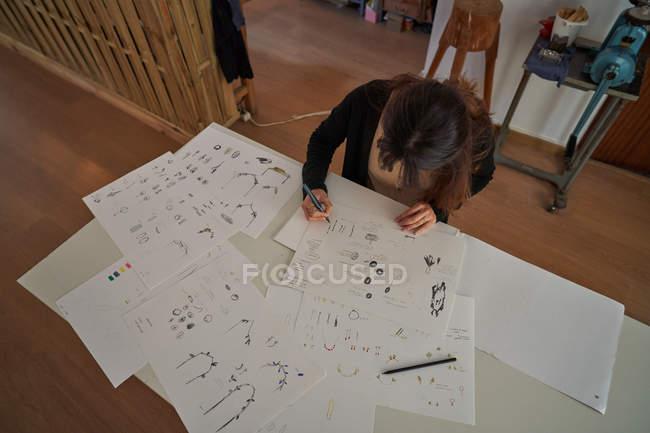 Mujer sentada en una mesa con un lápiz dibujando joyas sobre papel - foto de stock