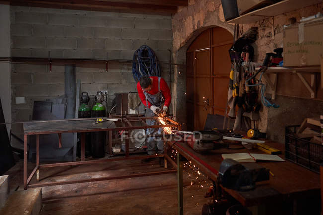 Interior of a workshop with a blacksmith working with the electric cutting disc — Stock Photo