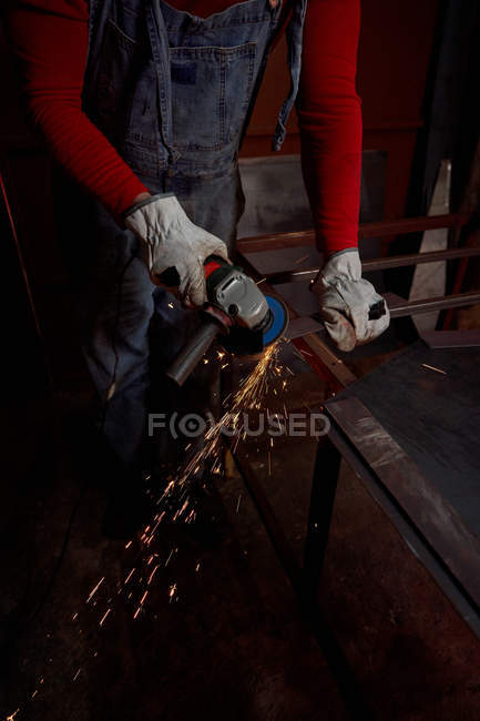 Blacksmith's hands working with the cutting disc while sparks are flying — Stock Photo