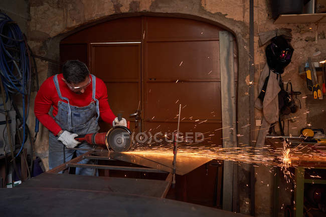 Blacksmith protected with glasses and gloves cutting iron with the cutting disc inside a workshop — Stock Photo