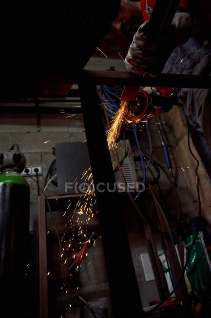 Снизу кузнец режет железо на металлическом столе — стоковое фото
