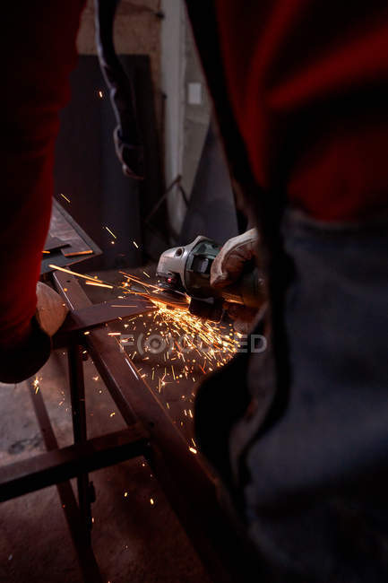 Crop unrecognizable hands of a blacksmith cutting metal with an electric cutting disc — Stock Photo