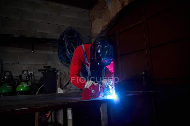 Кузнец работает в мастерской с электросварщиком — стоковое фото