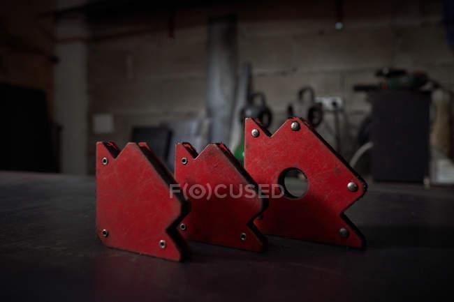 Pièces métalliques en forme de flèche rouge sur une table en métal dans une forge — Photo de stock