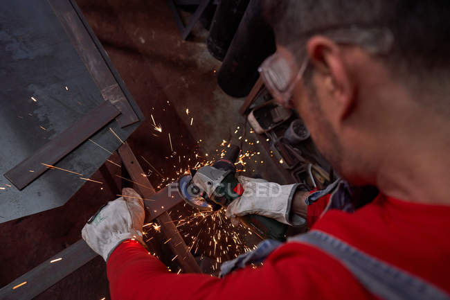 Blacksmith cutting metal with the electric cutting disc — Stock Photo