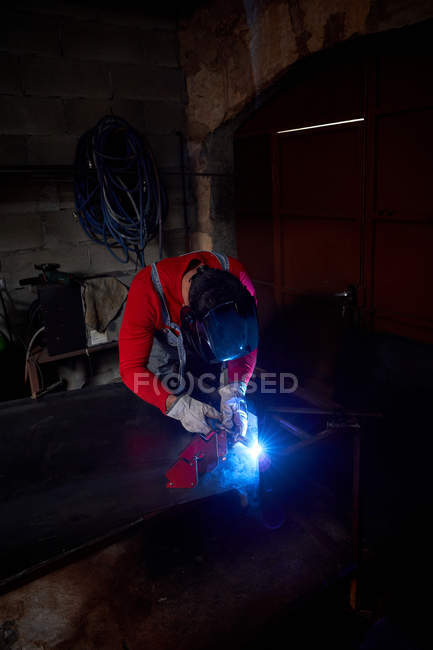 Blacksmith working in his workshop with an electric welder — Stock Photo