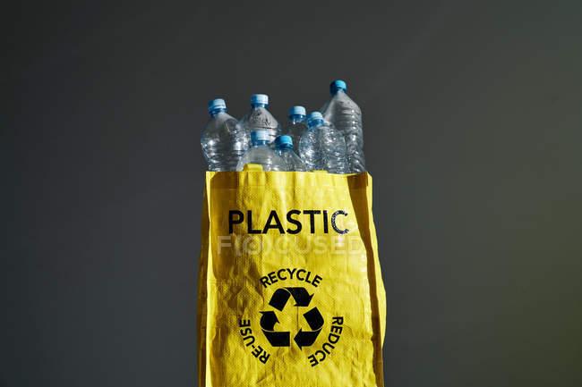 Ropa de botellas de agua vacía en bolsa amarilla con signo de reciclaje en fondo gris en estudio. - foto de stock