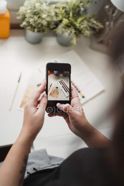 Unerkennbare Malerin fotografiert bei der Arbeit mit dem Smartphone — Stockfoto