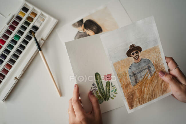 Unrecognizable female painter looking through drawings at workpl — Stock Photo