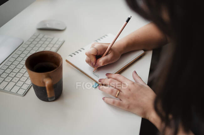 Faceless female freelancer making notes at table at workplace — Stock Photo