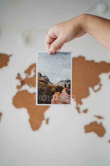 Anonymous woman holding picture in front of world map — Stock Photo