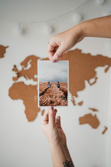 Анонімна жінка тримає фотографію перед картою світу. — стокове фото