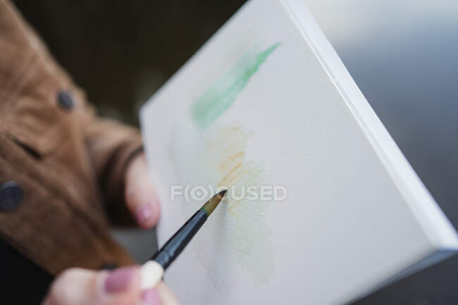 Woman standing at lakeside and drawing in notebook — Stock Photo