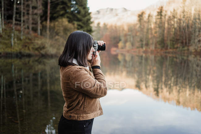 Woman taking photo at lakeside — Stock Photo