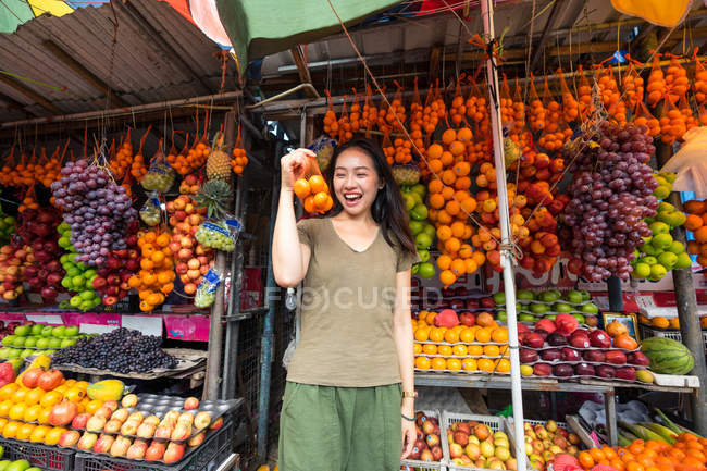 Joyful Asian female traveler enjoying fruits at outdoors market — Stock Photo