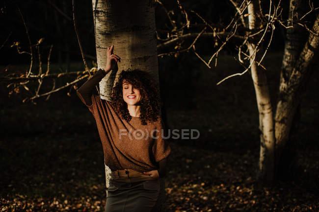 Приємна кучерява жінка в повсякденному одязі торкається осіннього жовтого листка і посміхається в лісі — стокове фото