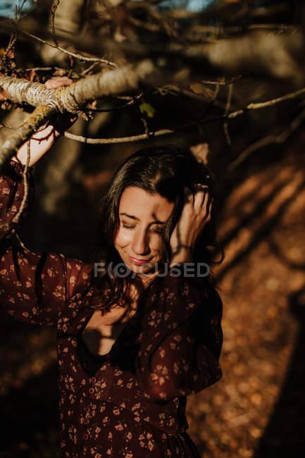 Mulher agradável em casual desgaste tocando folha amarela outono e sorrindo em madeiras — Fotografia de Stock