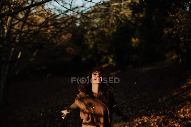 Надзвичайно вдоволена жінка в повсякденному одязі танцює в парку повні осінніх листків і посміхається — стокове фото