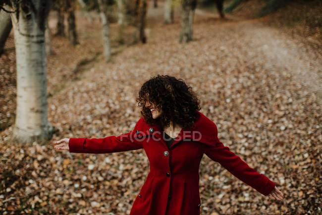 From above of curly haired woman smiling on golden fallen leaves on blurred background — Stock Photo