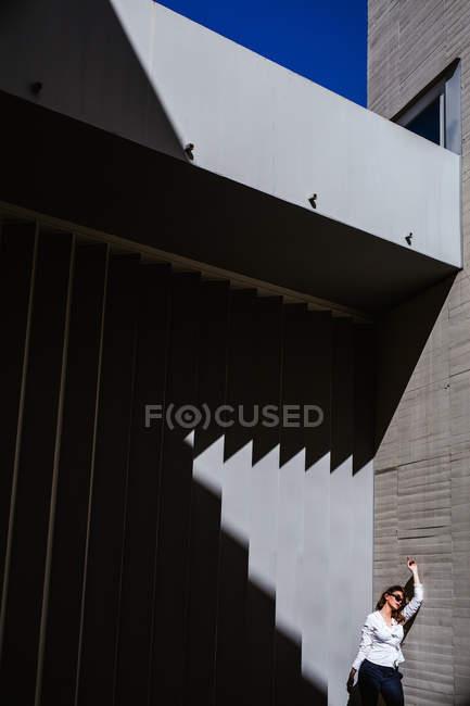 Молодая женщина в модных солнцезащитных очках и стильном наряде поднимает руку и опирается на стену современного здания в солнечный день — стоковое фото
