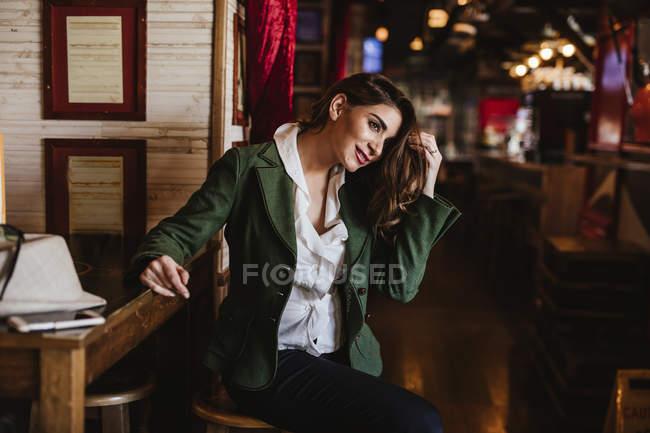 Trendy giovane donna in abiti alla moda sorridente e guardando altrove mentre riposava in accogliente caffè — Foto stock