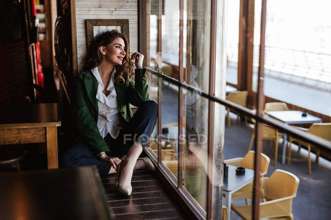 From above of pensive trendy woman sitting with crossed legs and looking through window of modern cafe — Stock Photo
