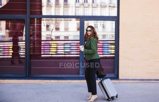 Побічний вид поважної жінки в класичному одязі і сонцезахисних окулярах, що дивляться у бік під час подорожі з сучасною валізою в аеропорт. — стокове фото
