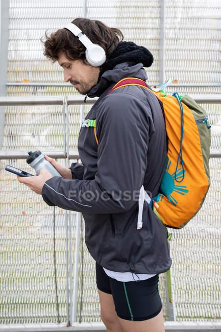 Vista laterale del jogger maschio in piedi in ponte chiuso con bottiglia thermos e cellulare in mano — Foto stock