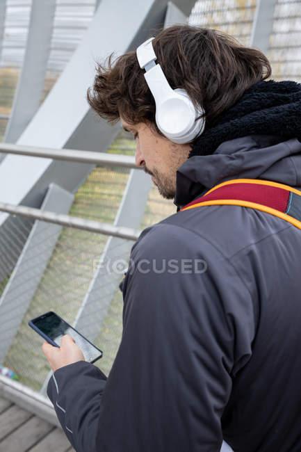 Jogger homme vêtu d'une veste chaude et d'un sac à dos se tenant debout dans un pont fermé avec un cellulaire à la main — Photo de stock