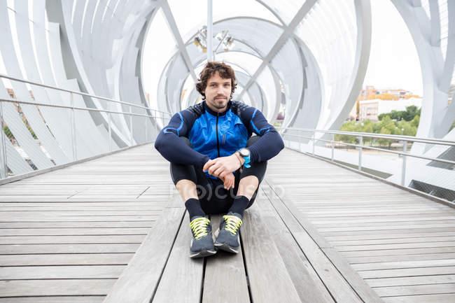 Jogador masculino em roupas de treino sentado no chão de madeira da ponte fechada descansando após o treino olhando para a câmera — Fotografia de Stock