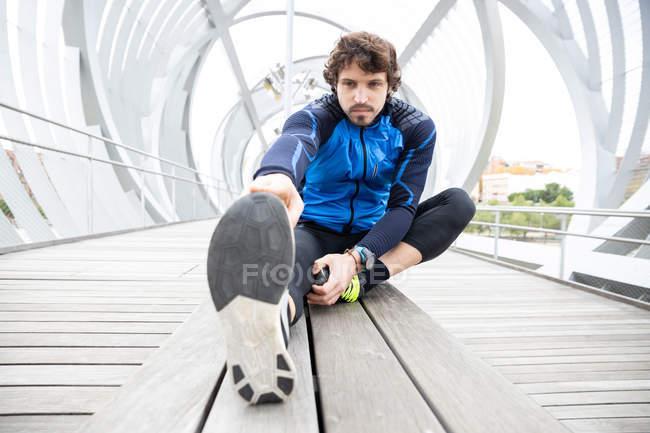 Maschio jogger in vestiti da allenamento seduti su terreno di legno di ponte chiuso e di eseguire esercizi di allungamento gamba — Foto stock