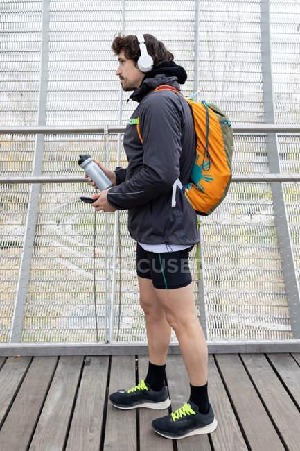 Vista laterale del jogger maschile in giacca calda e pantaloncini con zaino in piedi in ponte chiuso con bottiglia thermos e cellulare — Foto stock