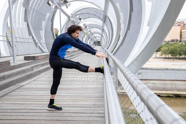 Vue latérale du joggeur debout sur la promenade et effectuant des exercices d'étirement de base sur le bar à la rive de la rivière pendant la journée — Photo de stock
