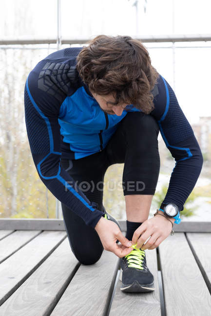 Male jogger in workout clothes doing up laces of sneakers during exercise on wooden boardwalk situated on river bank — Stock Photo
